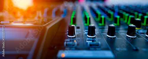 Fototapeta ็Music mix studio concept, hand control mixing sound console for good sound in concert, professional technology for musician engineer, board and buttons control for working on blurred background  obraz