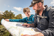 Father And Son Looking At Map While Hiking In Rural Prairie Landscape. Cody, Wyoming, USA