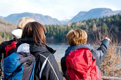 3 donne di mezza età osservano il panorama montano di un lago in Italia Canvas Print