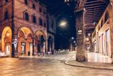 Fototapeta Uliczki - Old narrow street in Bologna, Emilia Romagna, Italy. Architecture and landmark of Bologna. Night cityscape of Bologna.