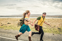 Couple Dressed In Vintage Clothes Running Down Rural Road. Cody, Wyoming, USA
