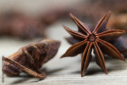 Photo star anise with or without seed, closed, on a light wooden surface