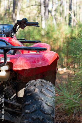 Red four wheeled ATV close up in the forest with a pine tree background ~DIRT~