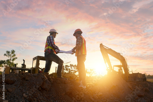 Engineers are working on road construction. engineer holdingradio communication at road construction site with roller compactor working dust road on during sunset