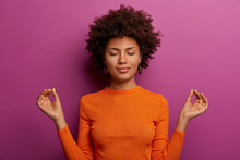 Peaceful Determined Curly Young Afro American Woman Makes Zen Gesture, Has Yoga Breathing Practice, Meditates Indoor, Closes Eyes And Wears Orange Jumper, Isolated Over Vibrant Purple Background