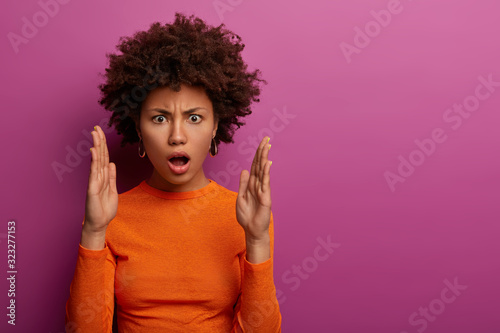 Photo Displeased emotional woman with Afro hairstyle shapes someting big, impressed ba