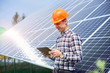 Leinwanddruck Bild Man in a helmet with a tablet in his hands near the solar cell station with a reflection of the sun in them. Home construction. Technology concept. Green ecological power energy generation