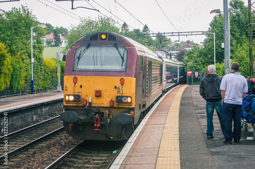 Famous scottish caledonian sleeper train is arriving to a platform on a train station on its way to Fort William on a cloudy day Tapéta, Fotótapéta