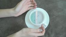 Ocean In The Cup. Girl's Hands...