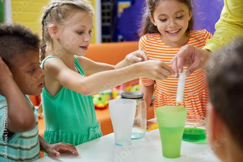 Carta da parati Kids doing chemical experiment at entertainment center