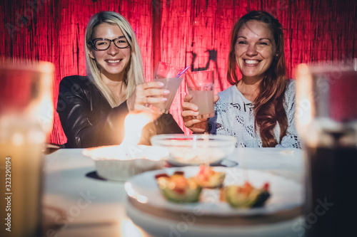 Fototapeta Two young women, a blonde and a redhead are cheering with glasses full of gin tonic drink and straws on a garden pary with candle on early evening obraz