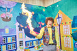 Funny entertainer showing chemical trick for kids. Flame in palm. Birthday party fire for kids.