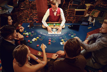 Group Of People Gambling Sitting At A Table In A Casino Top View