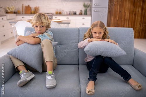 Blond cute girl with a pillow in her hands sitting next to her sad brother Canvas