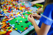 Little kid playing with lots of colorful plastic blocks indoor. Children playing toys inside school.
