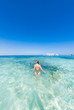 A girl in a green swimsuit to bathe in the blue water of the red sea. It's sunny outside