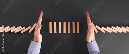 businessman protects his investment with two hands from falling dominoes Wallpaper Mural