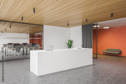 Reception table in white and orange office Fototapeta