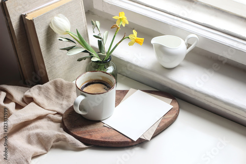 Fototapeta Cozy Easter spring still life. Greeting card mockup scene. Cup of coffee, books, wooden cutting board, milk pitcher and vase of flowers on windowsill. Floral composition. Yellow daffodils and tulip. obraz