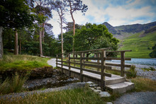 Footbridge Over Small Stream Next To Buttermere Lake And Mountains In Cumbria Lake District.