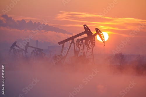 The oil pumping units by lakeside sunrise.