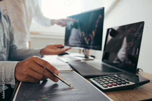 Fototapeta Close up of pen investors are working together with analyzing the stock data graphs in the paper and viewing the data on the laptop screen. obraz