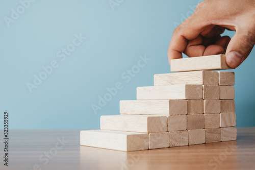 Fototapeta Business concept of ladder career path and growth success process. Hands of men arranging wood cube block stacking as step stair. obraz
