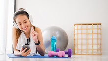 Asian Woman Listening To Music With Headphone And Smartphone After Play Yoga And Exercise At Home Background With Copy Space.Exercise For Lose Weight, Increase Flexibility And Tighten The Shape.