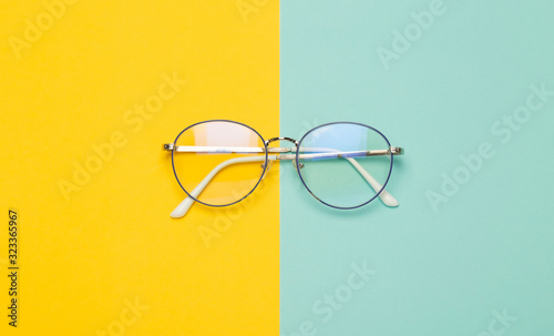 Obraz Eye glasses isolated on yellow and blue background. - fototapety do salonu