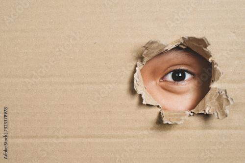 Boy eye peeking through a hole on a cardboard box with shocking gesture Fototapete