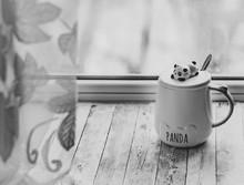 A White Mug With A Panda Figur...