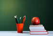 Back to school, orange pencil holder, stack of books on white table with red apple, empty green school board background, education concept.