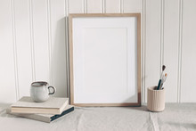 Blank Wooden Frame Mockup With Paint Brushes, Pencils In Ceramic Holder, Cup Of Coffee And Books On Linen Tablecloth. Artistic Scene. Creative Table Background. Poster Product Design, Wooden Wall.