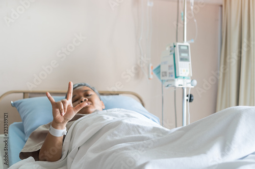 Fotografiet Happy Asian Patient hand sign in i love you laying on bed in hospital with medical drip intravenous needle, give salt water when her get well after treatment or surgery