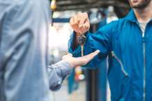 Auto Service. Handsome Young Auto Mechanic In Uniform Is Returning Car Key To A Client, Both Are Smiling.Customer Giving Him Car Keys To Mechanic In Service