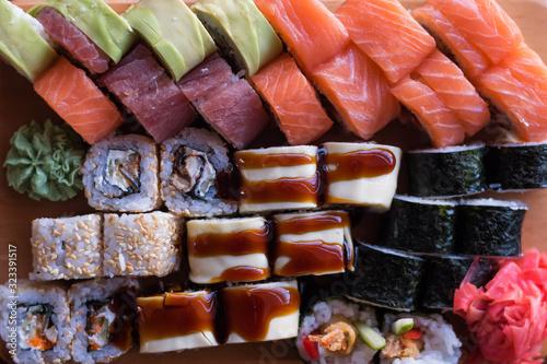 Fototapeta Maki and rolls with tuna salmon and avocado. Japanese and Asian food. Sushi Set. obraz