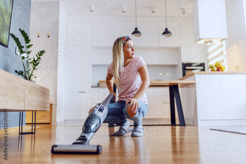 Fototapeta Worthy caucasian blond housewife crouching in living room and using steam cleaner to clean parquet. obraz