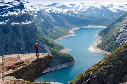 Photo Hiker woman standing on a cliff over a lake, Trolltunga, Norway