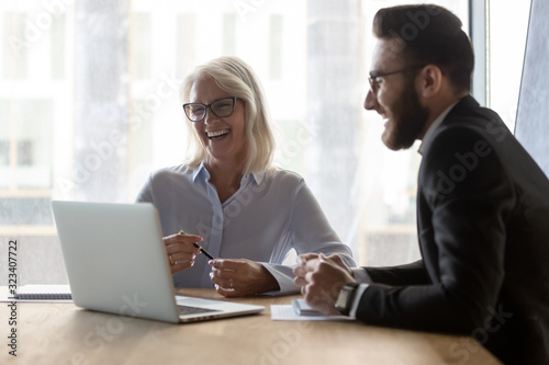 Photo Cheerful younger colleague helps to older woman with computer app