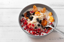 Plate Of Oatmeal With Fruit, Porridge, Dried Apricots, Raisins, Pomegranates, Mandarin Slices On A White Background, Healthy Breakfast