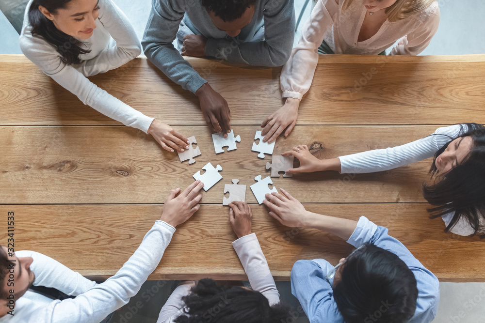 Fototapeta Multiracial team sitting around table, putting together puzzle pieces