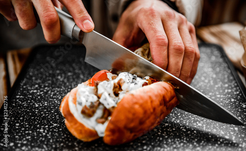 Foto man hand with knife cut Philly cheese steak sandwich with meat, vegetables, chee