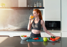 Athletic Girl With Gym Clothes Eats Fruit In The Kitchen
