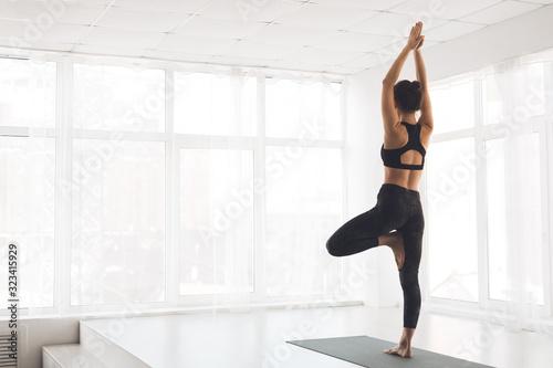Fotografia Woman exercising yoga in tree pose at home