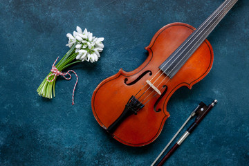 Fototapeta na wymiar Old Violin and Fresh beautiful bouquet of the first spring forest snowdrops flowers with red and white cord martisor - traditional symbol of the first spring day on classic blue background