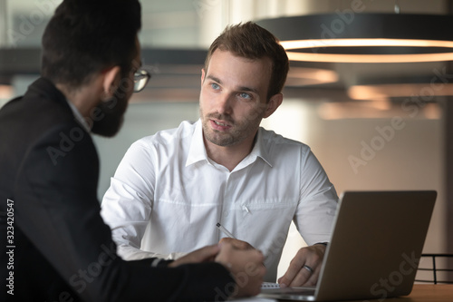 Fotografía European and arabian male colleagues talking seated at office desk