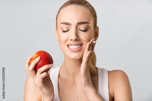 Carta da parati Young Woman Having Tooth Pain Eating Apple On Gray Background