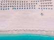 Aerial View from top to bottom to the beach with umbrellas and loungers on the shores of the beautiful turquoise sea. Greece.