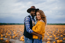 Happy Couple Stands In Pumpkin Field And Hugs