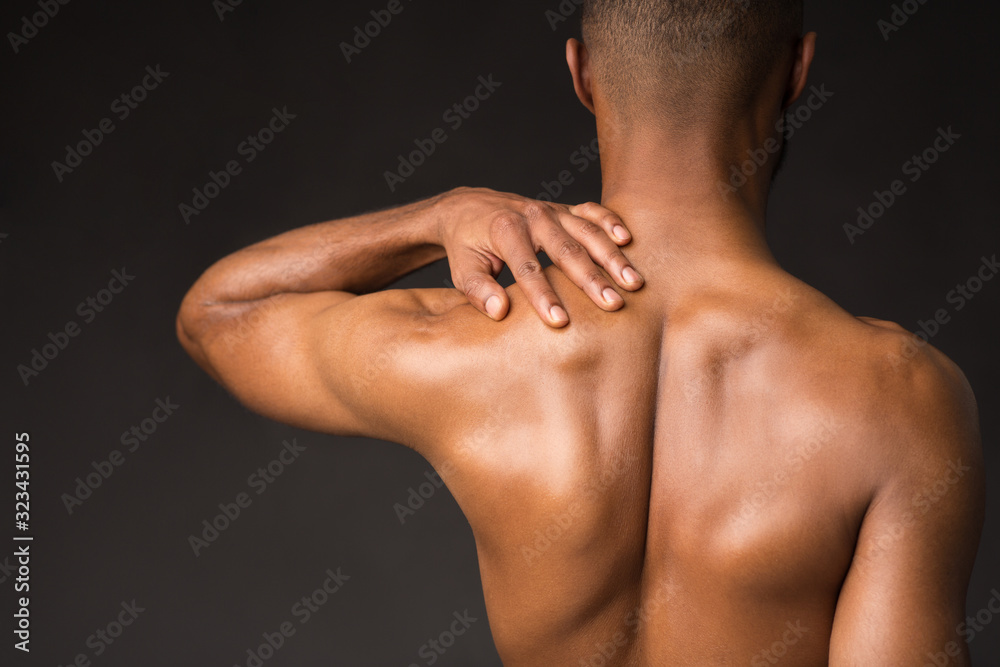 Fototapeta Shirtless black man doing neck and shoulder massage